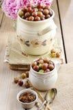 Krug Stachelbeeren auf Holztisch Stockfoto