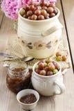 Krug Stachelbeeren auf Holztisch Stockfotos