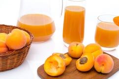 Krug und Gläser Aprikosensaft mit ganzem und geschnittenem reifem apri Lizenzfreies Stockbild