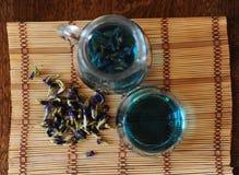 Krug und Glas mit blauem thailändischem Anchan-Tee auf Bambusmatte auf Holztisch Seifenerz von Blumen für das Brauen, Draufsicht Lizenzfreies Stockfoto