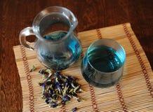 Krug und Glas mit blauem thailändischem Anchan-Tee auf Bambusmatte auf Holztisch Seifenerz von Blumen für das Brauen, Draufsicht Lizenzfreie Stockfotos