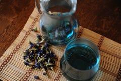 Krug und Glas mit blauem thailändischem Anchan-Tee auf Bambusmatte auf Holztisch Seifenerz von Blumen für das Brauen, Draufsicht Lizenzfreie Stockfotografie