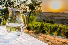Krug Wasser auf Tabelle in der Landschaft Lizenzfreies Stockbild