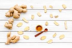 Kruid en specerij De grondgember in kleine kom sneed dichtbij gemberwortel op witte houten hoogste mening als achtergrond stock foto