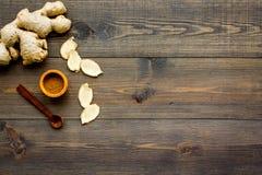 Kruid en specerij Grondgember in kleine kom dichtbij gemberwortel op de donkere houten ruimte van het achtergrond hoogste menings stock afbeelding