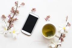 Kruiden gezonde dranken hete groene thee met mobiele telefoon stock afbeelding