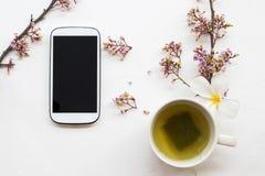 Kruiden gezonde dranken hete groene thee met mobiele telefoon stock foto