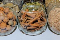 Kruiden in glasflessen: pijpjes kaneel, notemuskaat, koriander royalty-vrije stock foto's