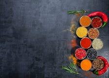 Kruiden Kleurrijke Kruiden Kerrie, Saffraan, kurkuma, kaneel en otheron een donkere concrete achtergrond Peper Grote inzameling v Stock Foto