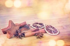 Kruiden met droge sinaasappel en kaneel op houten achtergrond met vaag lightsr Stock Afbeelding