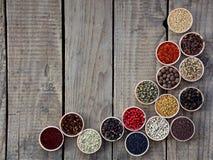 Kruiden op een houten achtergrond Koriander, zwarte peper, paprika, mosterd, kurkuma, komijn, sumac, fenegriek, kruidnagels, cube Stock Foto's