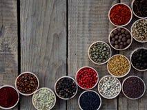 Kruiden op een houten achtergrond Koriander, zwarte peper, paprika, mosterd, kurkuma, komijn, sumac, fenegriek, kruidnagels, cube Stock Fotografie