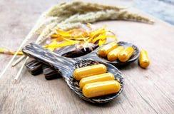 Kruidengeneeskundeaard/Natuurlijke Uittrekselkurkuma voor de Gele capsules van de kruidgeneeskunde op houten lepel stock foto's