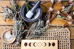 Kruidenheksenmortier en stamper met maanfasen, tak pentagram en droge kruidbundels op rustieke achtergrond stock fotografie