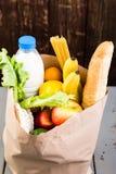 Kruidenierswinkel het winkelen concept Verschillend voedsel in document zak op houten achtergrond stock fotografie