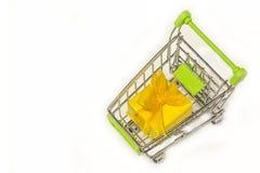 Kruidenierswinkelkar op een witte achtergrond met een gele giftdoos, een doos met een boog, Stock Afbeeldingen