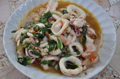 Kruidig beweeg gebraden calamari met basilicumbladeren stock afbeeldingen