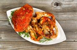 Kruidige gekookte krab klaar om op witte plaat met rustiek hout te dienen royalty-vrije stock foto