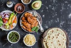 Kruidige geroosterde kip, tortilla, avocado, kaas, groenten op een donkere achtergrond stock foto