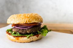 Kruidige hamburger op houten lijst grijze achtergrond stock foto