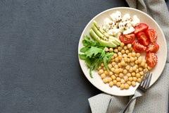 Kruidige kekers, avocado, tomaten, arugulakom op donkere achtergrond, hoogste mening Heerlijk evenwichtig voedselconcept royalty-vrije stock afbeelding