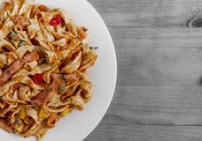 Kruidige spaghetti met tomatendeegwaren op een witte plaat op een zwart-witte achtergrondexemplaarruimte royalty-vrije stock afbeeldingen