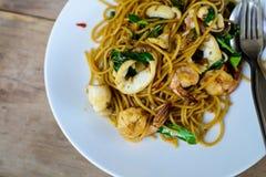 Kruidige spaghetti met zeevruchten op houten lijst Stock Foto