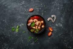 Kruidige Thaise soep Tom Yam met seafoodon op een uitstekende gekleurde achtergrond met ingrediënten Hoogste mening Stock Foto