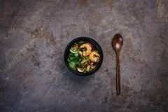 Kruidige Thaise soep Tom Yam met zeevruchten in een zwarte kom op een uitstekende gekleurde achtergrond met een houten lepel Hoog stock afbeelding