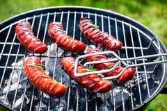 Kruidige worsten met kruiden en rozemarijn op een grill Royalty-vrije Stock Foto