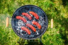 Kruidige worsten met rozemarijn op een grill Royalty-vrije Stock Afbeelding