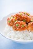 Kruidige zoete en zure kip met sesam en rijst op blauwe houten dichte omhooggaand als achtergrond Royalty-vrije Stock Foto