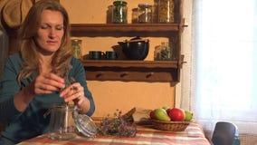 Kruidkundigemeisje gezette orego in glas Oude landelijke ruimte 4K stock video