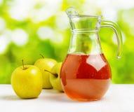 Kruik appelsap op aardachtergrond Stock Foto