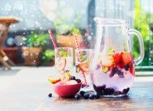 Kruik en glazen met bessen gegoten water op lijst in tuin stock afbeeldingen