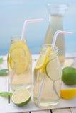 Kruik en glazen met limonade, citroenen en kalk op rustieke lijst Royalty-vrije Stock Afbeeldingen