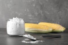 Kruik en lepel met maïszetmeel op lijst stock foto