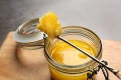 Kruik en lepel met verduidelijkte boter royalty-vrije stock afbeeldingen