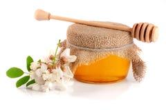 Kruik honing met bloemen van acacia op witte achtergrond wordt geïsoleerd die Royalty-vrije Stock Afbeelding