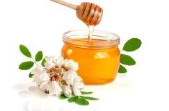 Kruik honing met bloemen van acacia op witte achtergrond wordt geïsoleerd die Royalty-vrije Stock Foto