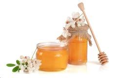 Kruik honing met bloemen van acacia op witte achtergrond wordt geïsoleerd die Royalty-vrije Stock Afbeeldingen