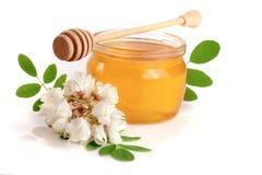 Kruik honing met bloemen van acacia op witte achtergrond wordt geïsoleerd die Stock Foto's