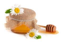 Kruik honing met bloemen van kamille op witte achtergrond wordt geïsoleerd die stock foto