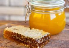 Kruik honing met honingraat Stock Afbeeldingen