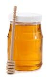Kruik honing met houten stok stock foto's