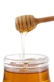 Kruik honing met houten stok stock foto
