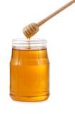 Kruik honing met houten stok stock fotografie