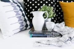 Kruik, koffiekop en boeken met kleurrijke hoofdkussens op achtergrond Stock Foto