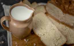 Kruik melk en een brood van brood op een houten raad stock fotografie