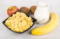 Kruik melk, kom met cornflakes en vruchten Stock Foto's